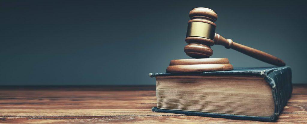 Domstolsklubba och lagbok på ett träbord
